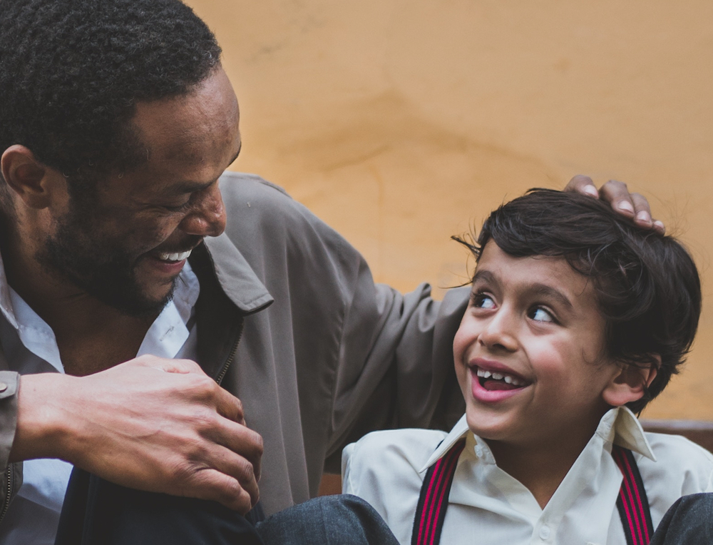boy grins, bright eyes, as his dad connects with him after a game of soccer on a poor street